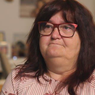 Heike Frohnhöfer, eine Frau mit dunkelroten Haaren und Brille, blickt traurig von der rechten in die linke Bildhälfte (Foto: SWR)
