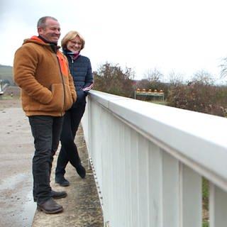 Elke und Thomas schauen von einem Brückengeländer auf die Straße und lächeln (Foto: SWR)