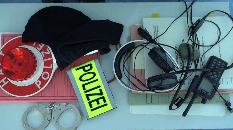 Polizeiausrüstung: Handschelle, Kelle, Funkgerät und Akten liegen auf einem Tisch (Foto: SWR)