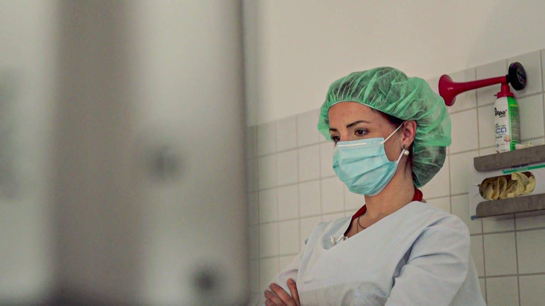 Junge Frau mit Netzhaube in Behandlungsraum (Foto: SWR)