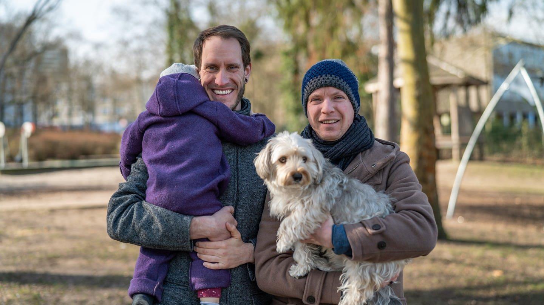 Zwei junge Männer halten ein Kleinkind und einen Hund auf dem Arm (Foto: SWR)