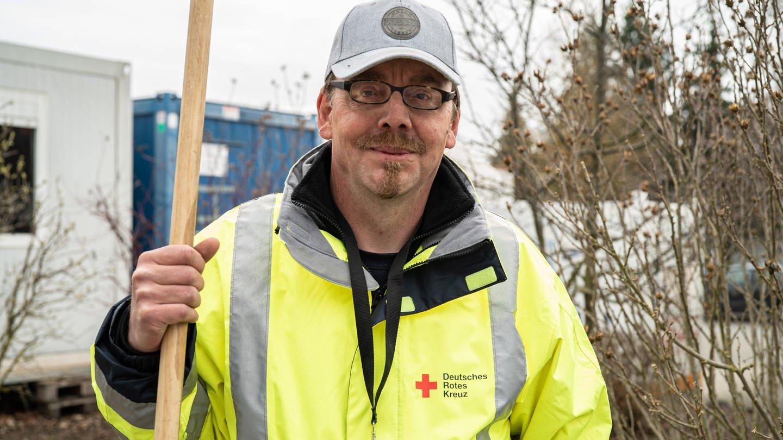 Mann in Neongelber Arbeitsweste mit Besen in der Hand (Foto: SWR)