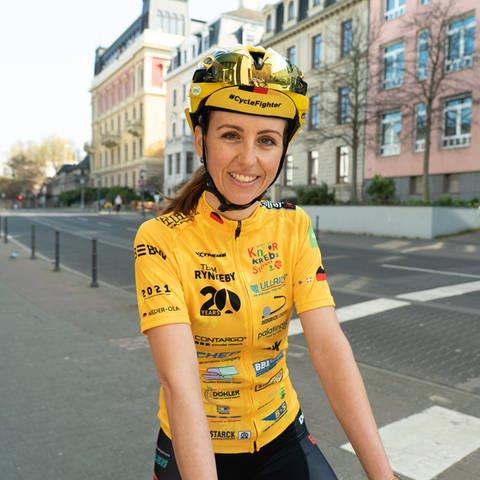Lea, Mitte 30, in ihrem gelben Rennradoutfit bedruckt mit Sponsoren (Foto: SWR)