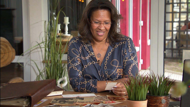 Mittelalte Frau sitzt an Tisch und schaut sich Fotos an