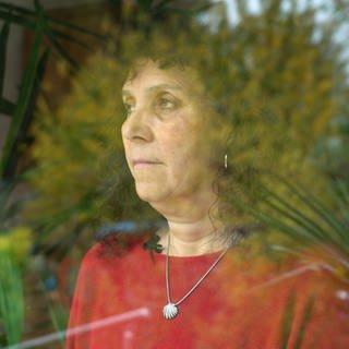 Traurige Frau steht an einem Fenster und blickt in die Ferne (Foto: SWR)