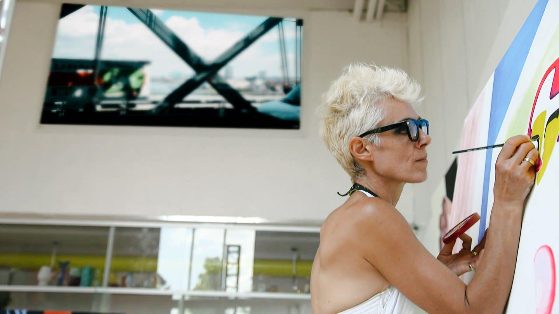 Eine Frau mit kurzen blonden Haaren steht vor einer großen Leinwand und malt darauf in bunten Farben (Foto: SWR)