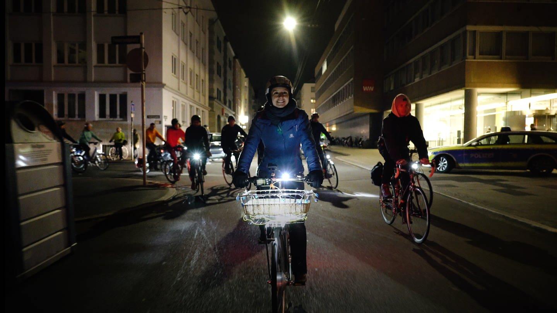 Frau in blauer Jacke fährt in der Gruppe durch Stuttgart Fahrrad. Es is nachts. (Foto: SWR)