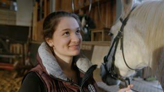 Kassandra hält ein Pferd am Halfter (Foto: SWR)