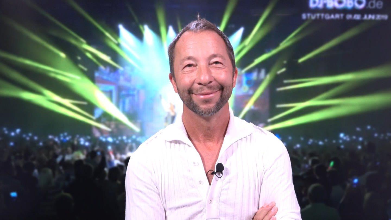 DJ Bobo lächelt in die Kamera. Im Hintergrund lässt sich ein Konzert erahnen. (Foto: SWR)
