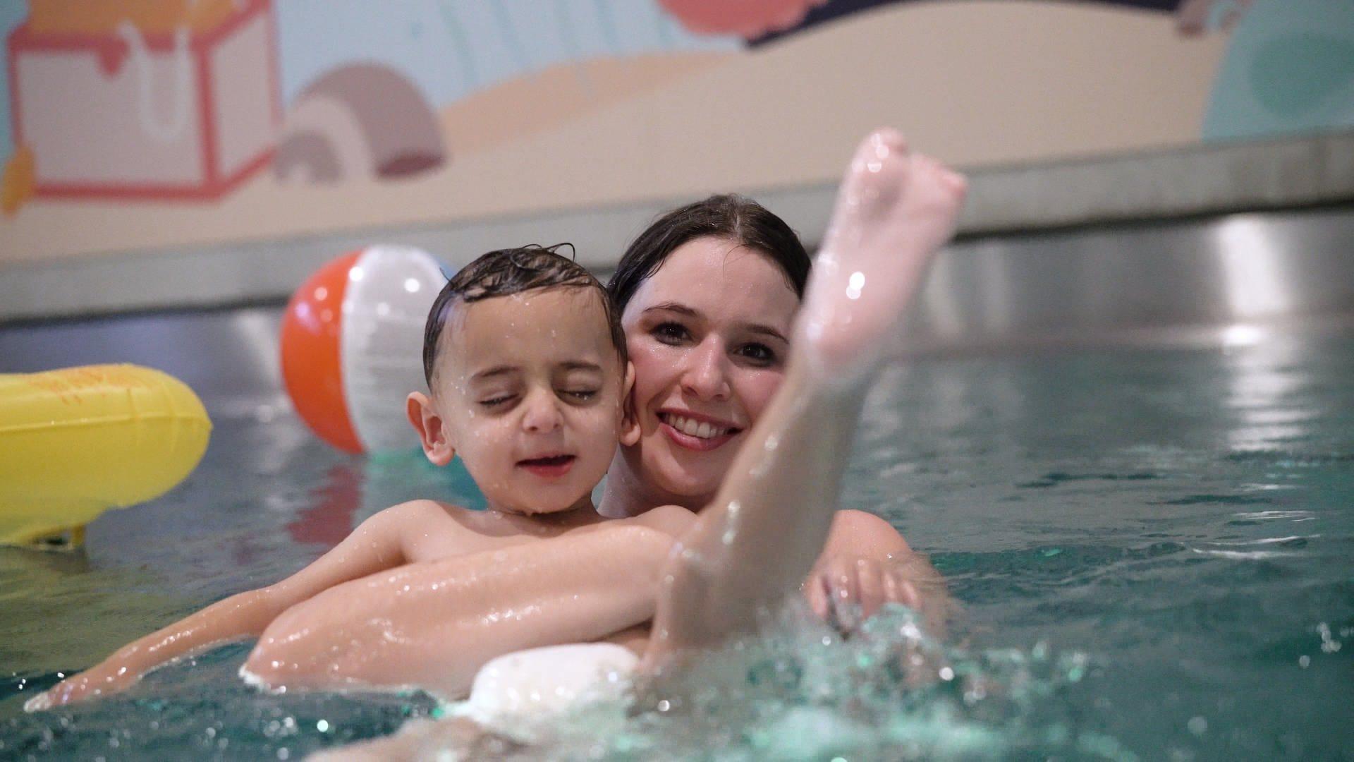 Eine Fau badet mit einem Kind im Kinderhospiz in Stuttgart.