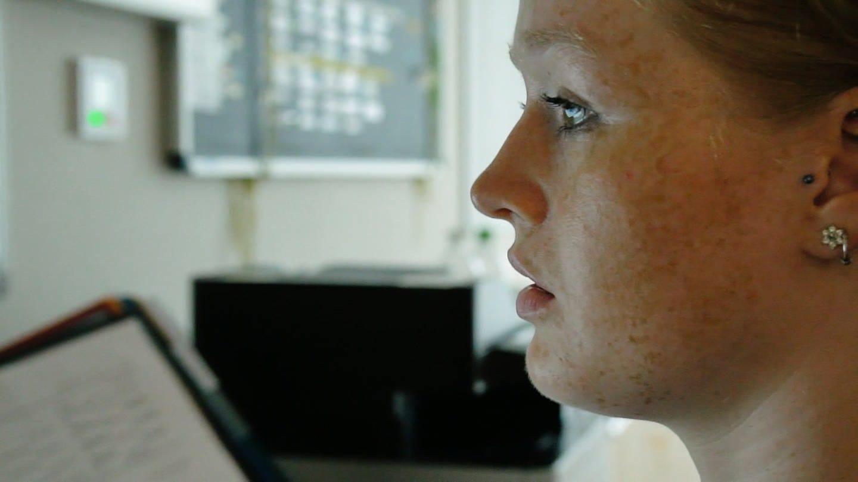 Eine junge Pflegefraft schaut gestresst. (Foto: SWR)
