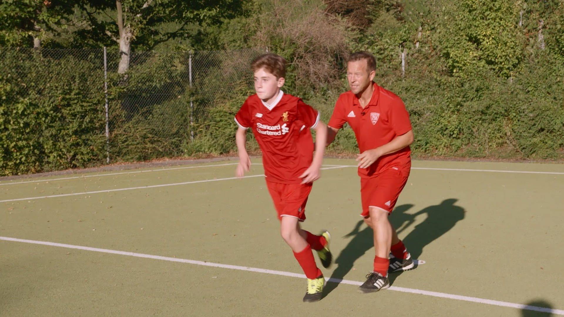 Fußballtrainer in rotem Trikot trainiert Jugendspieler