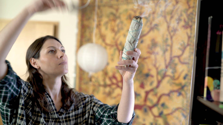 Junge Frau räuchert mit weißem Salbei eine Wohnung aus (Foto: SWR)