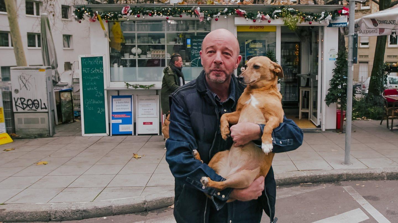 Mann mit Hund auf dem Arm vor einem Kiosk (Foto: SWR, SWR)