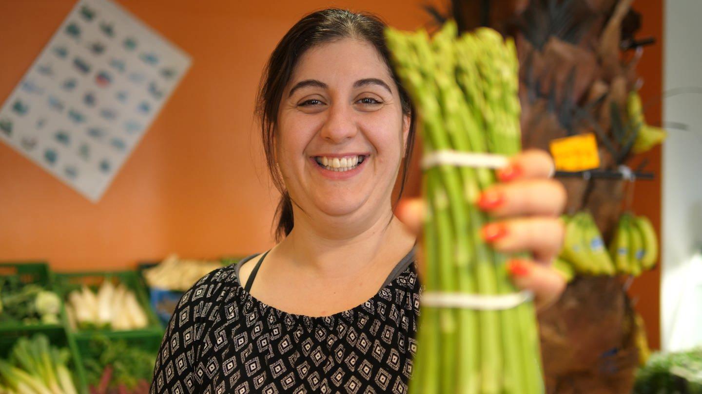 Noura hält einen bund grünen Spargel in die Kamera und lächelt dabei. (Foto: SWR)