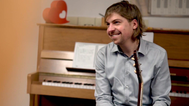 Philipp sitzt auf einem Stuhl, hält seine Gitarre in der Hand und lächelt. (Foto: SWR)