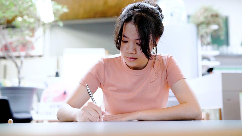 Pim aus Thailand und Stuttgart sitzt an einem Tisch und schreibt einen Brief (Foto: SWR)