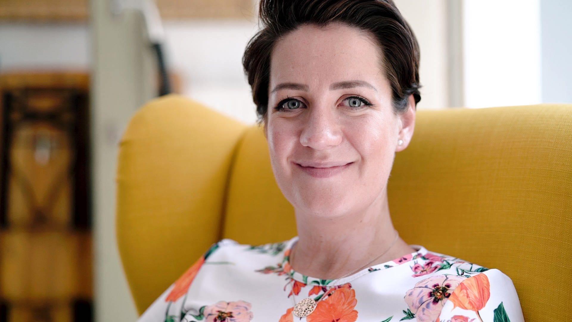 Sandra aus Stuttgart ist brünett, sitzt auf einem gelben Sessel und schaut in die Kamera