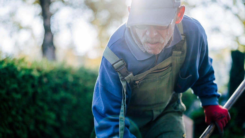 Willi ist Friedhofsgärtner. Er arbeitet gerade und befreit unter anderem Gräber vom gefallenen Laub. (Foto: SWR)