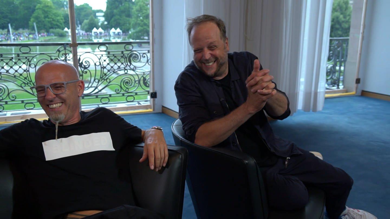 Zwei prominente Deutschrapper sitzen lächelnd auf Stühlen (Foto: SWR)
