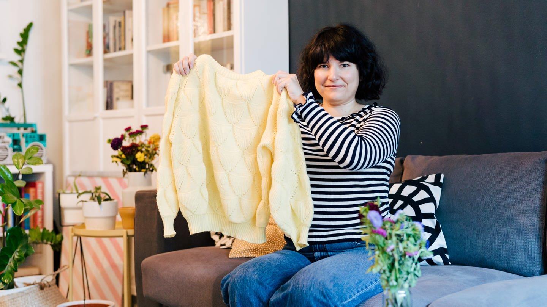 Eine junge Frau hält einen gelben Retro-Pullover in die Kamera (Foto: SWR)