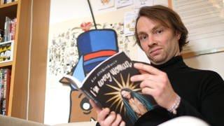 Porträt Junger Mann hat einen Comic in der Hand (Foto: SWR)