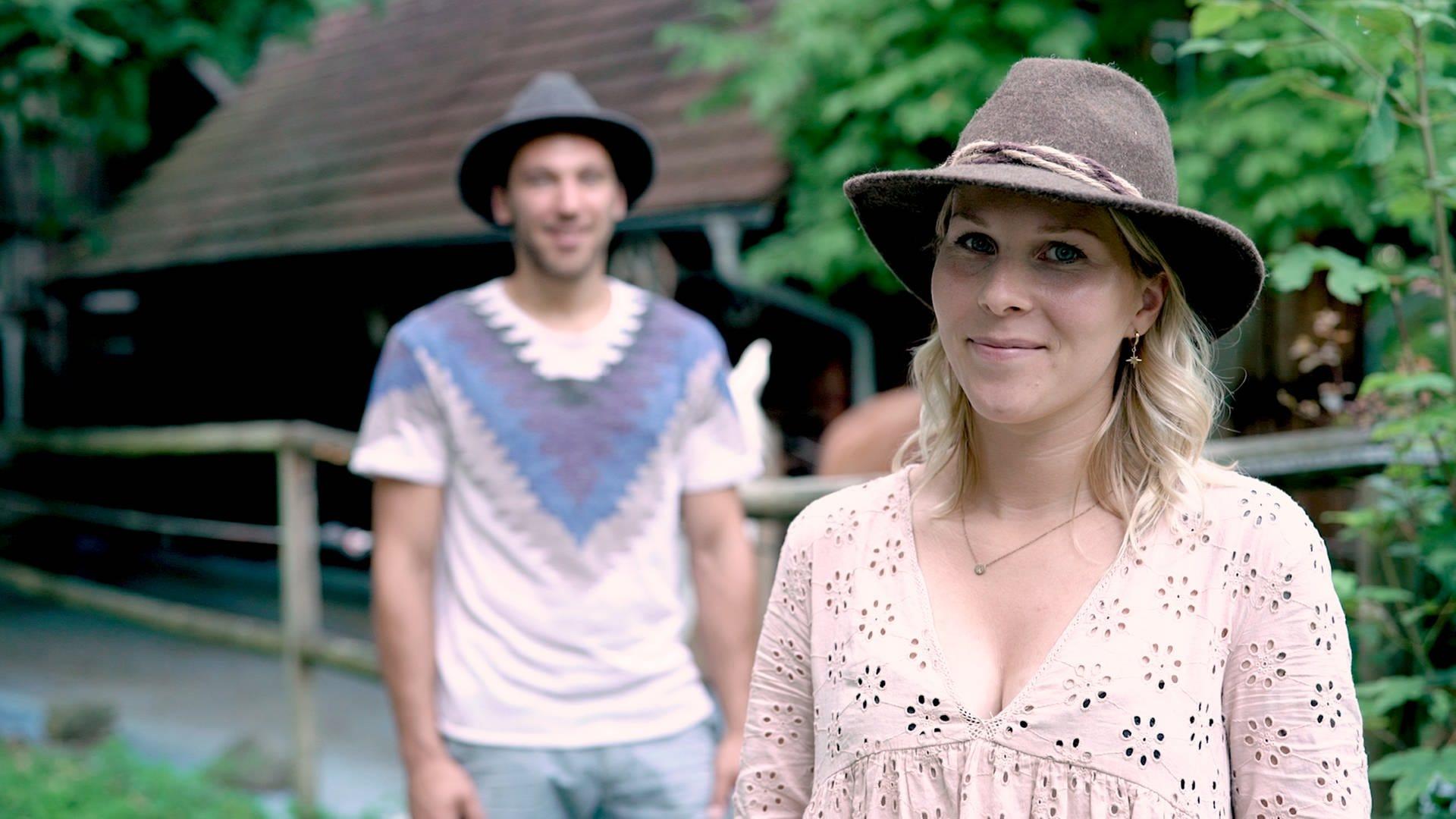 Amira hat einen braunen Hut auf und lächelt in die Kamera