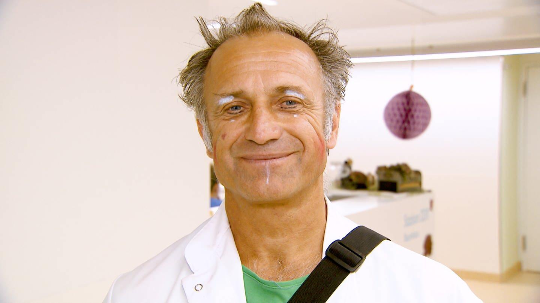 Andreas ist Klinikclown. Er hat graues Haar, ist geschminkt und  lächelt in die Kamera. (Foto: SWR)