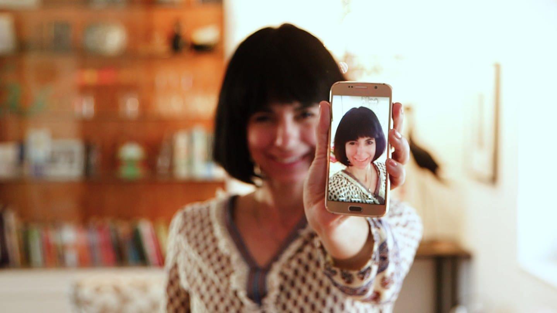 Junge Frau hält ein Handy mit ihrem Selfie in die Kamera (Foto: SWR)
