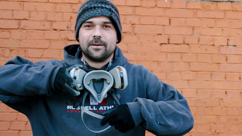 Junger Mann mit Atemschutzmaske um den Hals steht vor Klinkermauer (Foto: SWR)