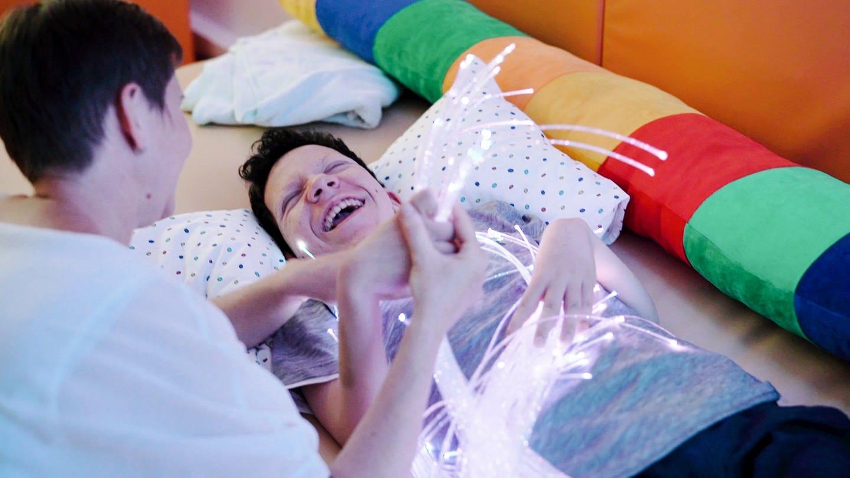 Behinderter Junge liegt lachend in einem Bett (Foto: SWR)