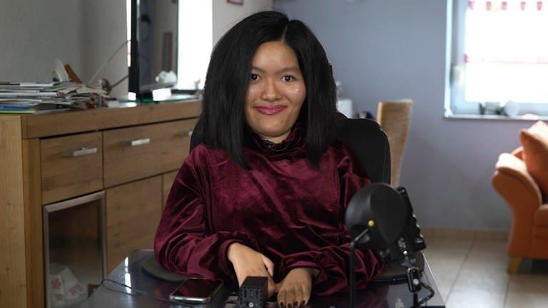 Eine junge Frau sitzt im Rollstuhl