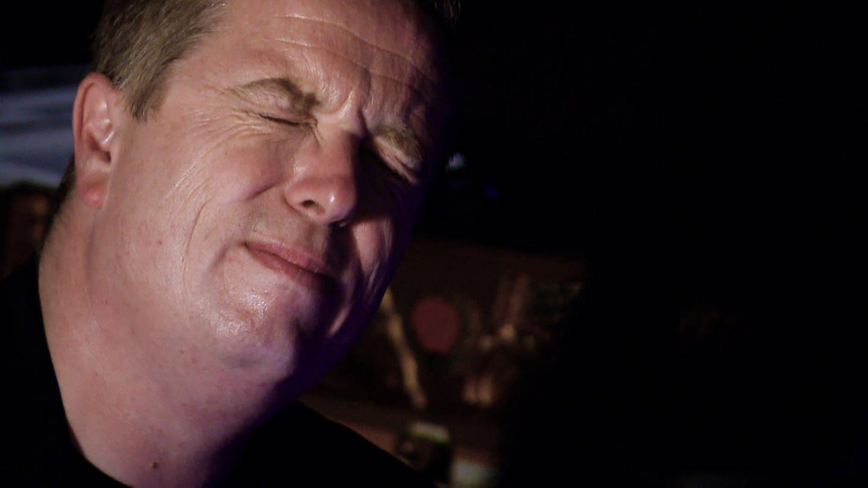 Gesicht eines Mannes im Dunkeln ganz nah, sein Ausdruck ist fast schmerzverzerrt (Foto: SWR)