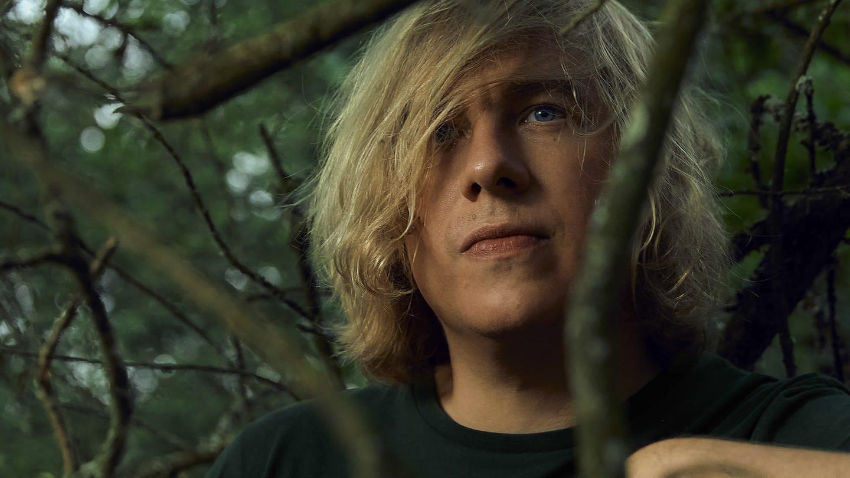 Junger Mann mit blonden langen Haaren im Gestrüpp (Foto: SWR)
