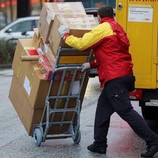Paketbote liiefert Pakete aus (Foto: dpa Bildfunk, Picture Alliance)