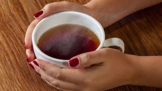 Frau umfasst eine Tasse mit Tee (Foto: Colourbox)