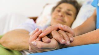Eine Krankenschwester hält die Hand einer älteren Frau (Foto: Getty Images)