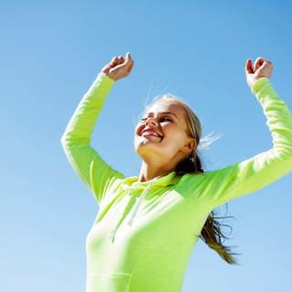 Glücklich: Frau streckt die Arme in Siegerpose nach oben und lächelt (Foto: Colourbox)