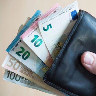 Hand hält Geldbeutel mit herausschauenden Geldscheinen (Foto: dpa Bildfunk, Picture Alliance)