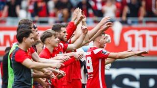 Die Spieler des FCK freuen sich gemeinsam mit ihren Fans über das Unentschieden gegen Waldhof Mannheim.