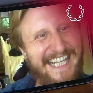 """Smartphone-Aufnahme von Michael Kranz, während er von der SWR Landesschau Moderatorin Jana Kübel erfährt, dass sein Film """"Was tun"""" den Publikumspreis des Deutschen Dokumentarfilmpresies 2021 gewonnen hat (Foto: SWR)"""