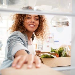 Eine Frau legt Lebensmittel in den Kühlschrank (Foto: Colourbox)