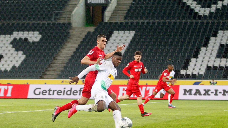 Der Mönchengladbacher Breel Embolo und der Kölner Ellyes Skhiri kämpfen um den Ball. Im Hintergrund sind leere Zuschauerränge zu sehen.