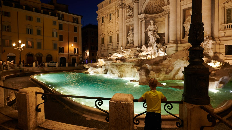 Ein Kind steht abends am Trevi-Brunnen, italienisch Fontana di Trevi, in Rom.