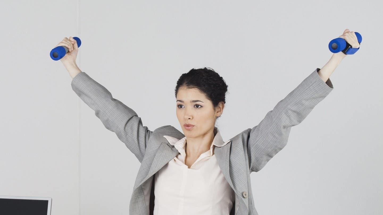 Junge Businessfrau trainiert im Büro mit Hanteln