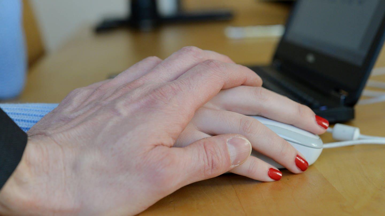 Mann belästigt eine Frau im Büro