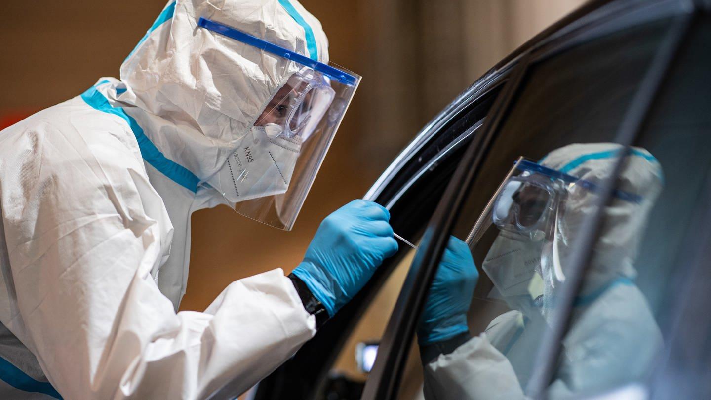 Ein Mitarbeiter nimmt in einem COVID-19-Drive-In-Testzentrum eine Probe (Foto: dpa Bildfunk, Picture Alliance)