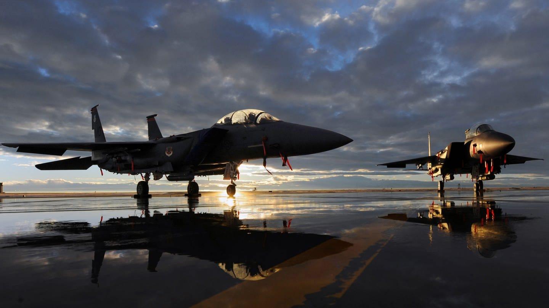 Ein Kampfjet, ein F-15 Strike Eagle fighter, steht zwischen Pfützen auf einem Rollfeld im Sonnenuntergang, im Hintergrund türmen sich dunkle Wolken auf.