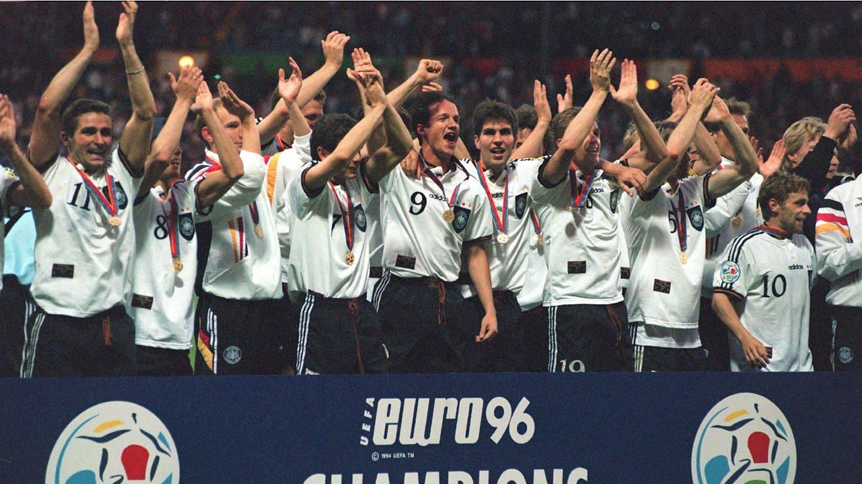 Deutsche Fußball-Nationalmannschaft jubelt am 30.6.1996 im Londoner Wembley-Stadion hinter dem Logo der EURO 96 gemeinsam über den Titelgewinn.