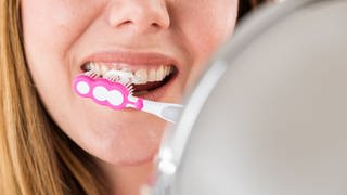 Eine junge Frau sitzt vor einem Spiegel und putzt sich die Zähne. (Foto: dpa Bildfunk, Christin Klose)